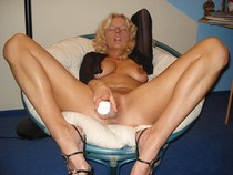 Cute milf masturbating with dildo on chair