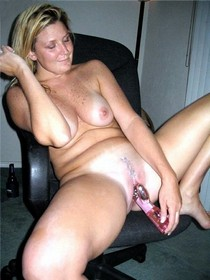 Mature lady enjoying a new sex toy right in her husband's office