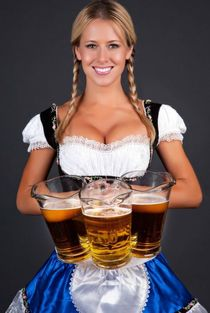 German barmaid in braids wearing dirndl and holding pitchers