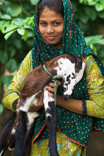 Beautiful Indian Girl posing with her lamb in a village ne.