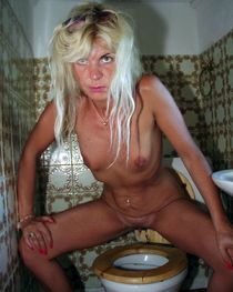 Skinny mature woman pissing in the toilet pan